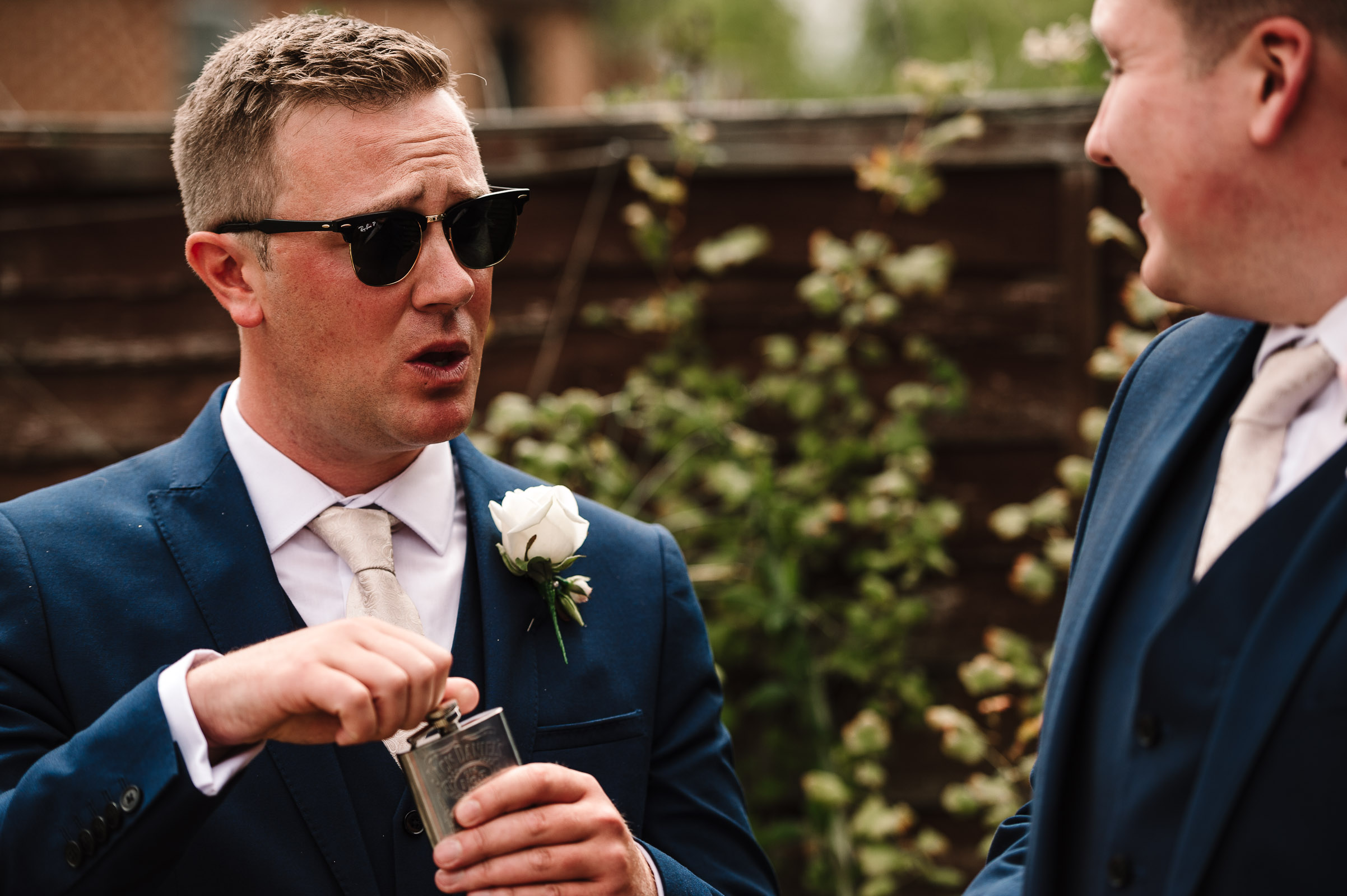 groom having a sip from hip flask