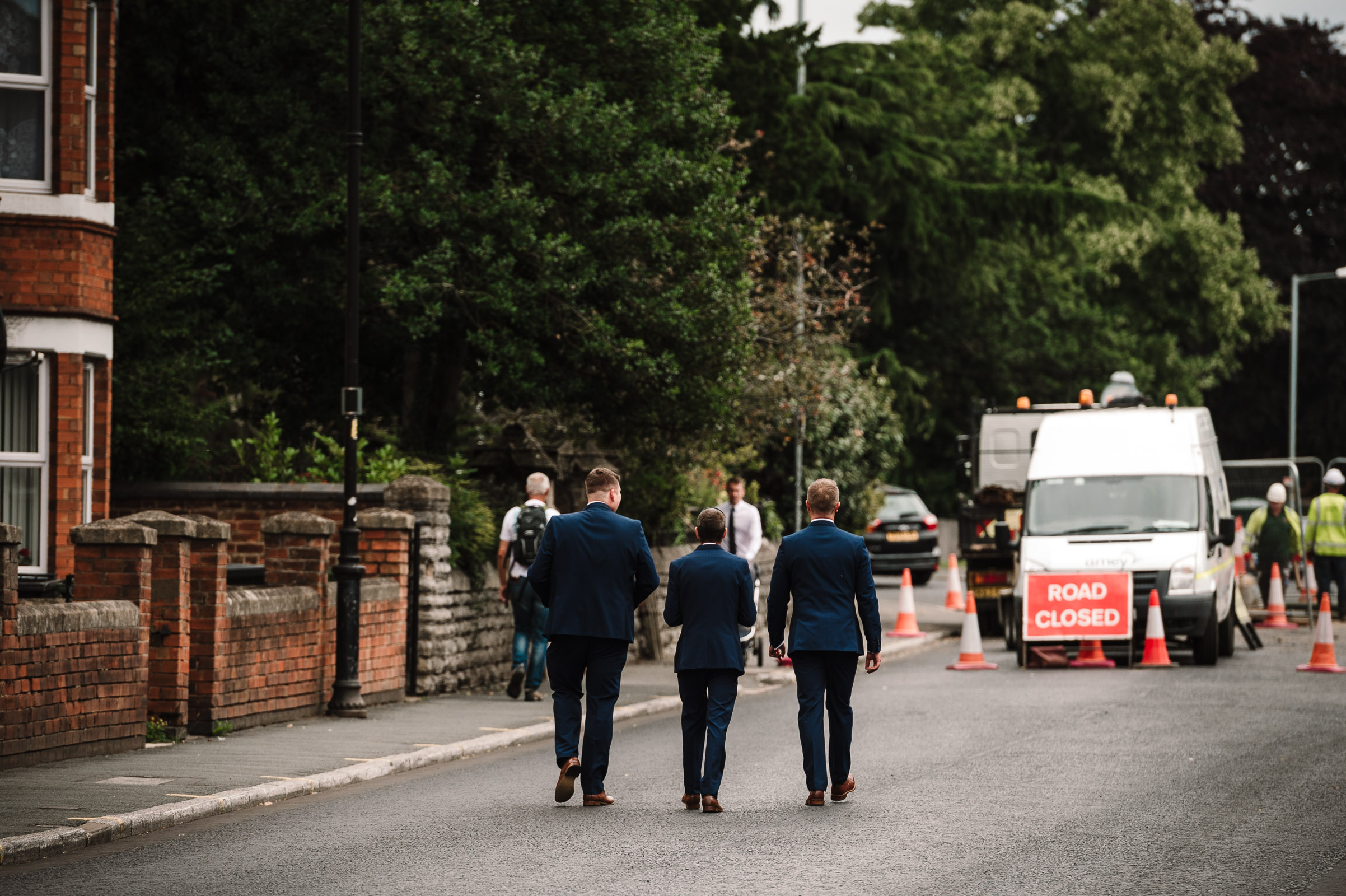 Groom and groomsmen walking down the road to church
