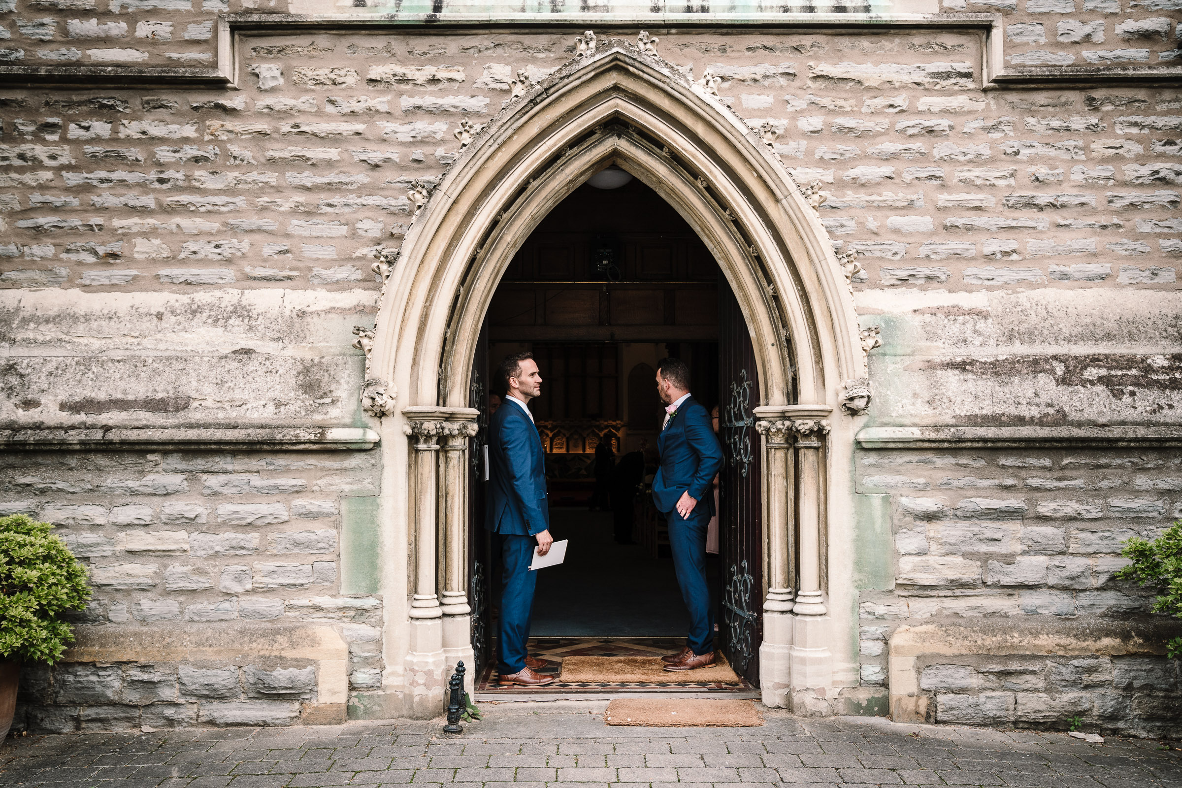 groomsmen waiting in the church entrance for guests