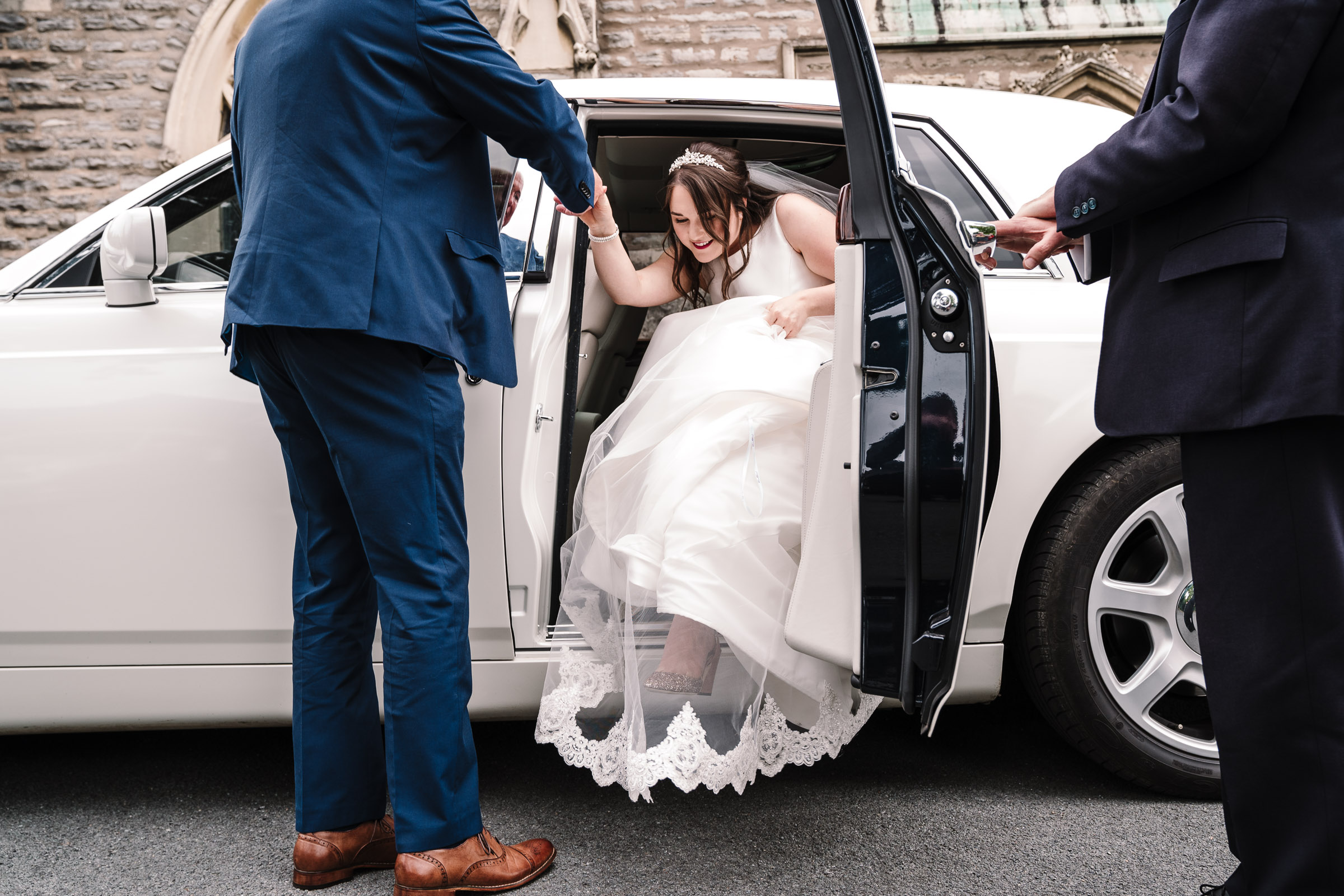 bride stepping out of wedding car outside church