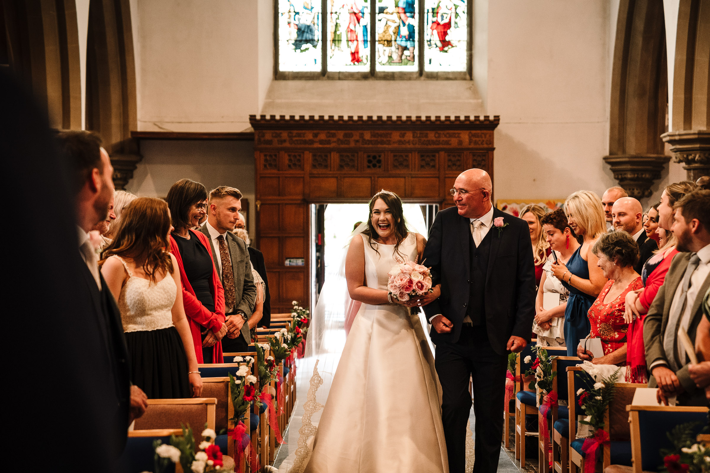 bride walking down the aisle with her father at church wedding