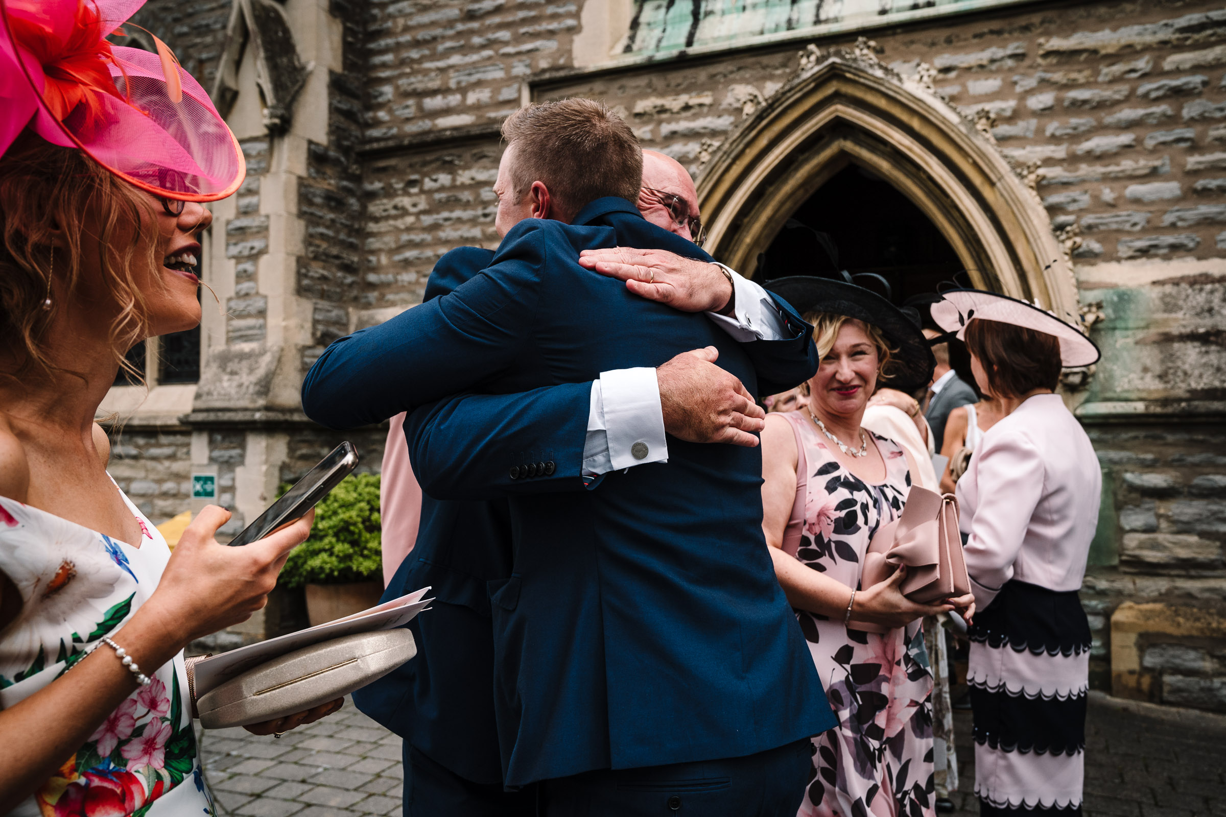 groom hugging father of the bride outside evesham church after wedding