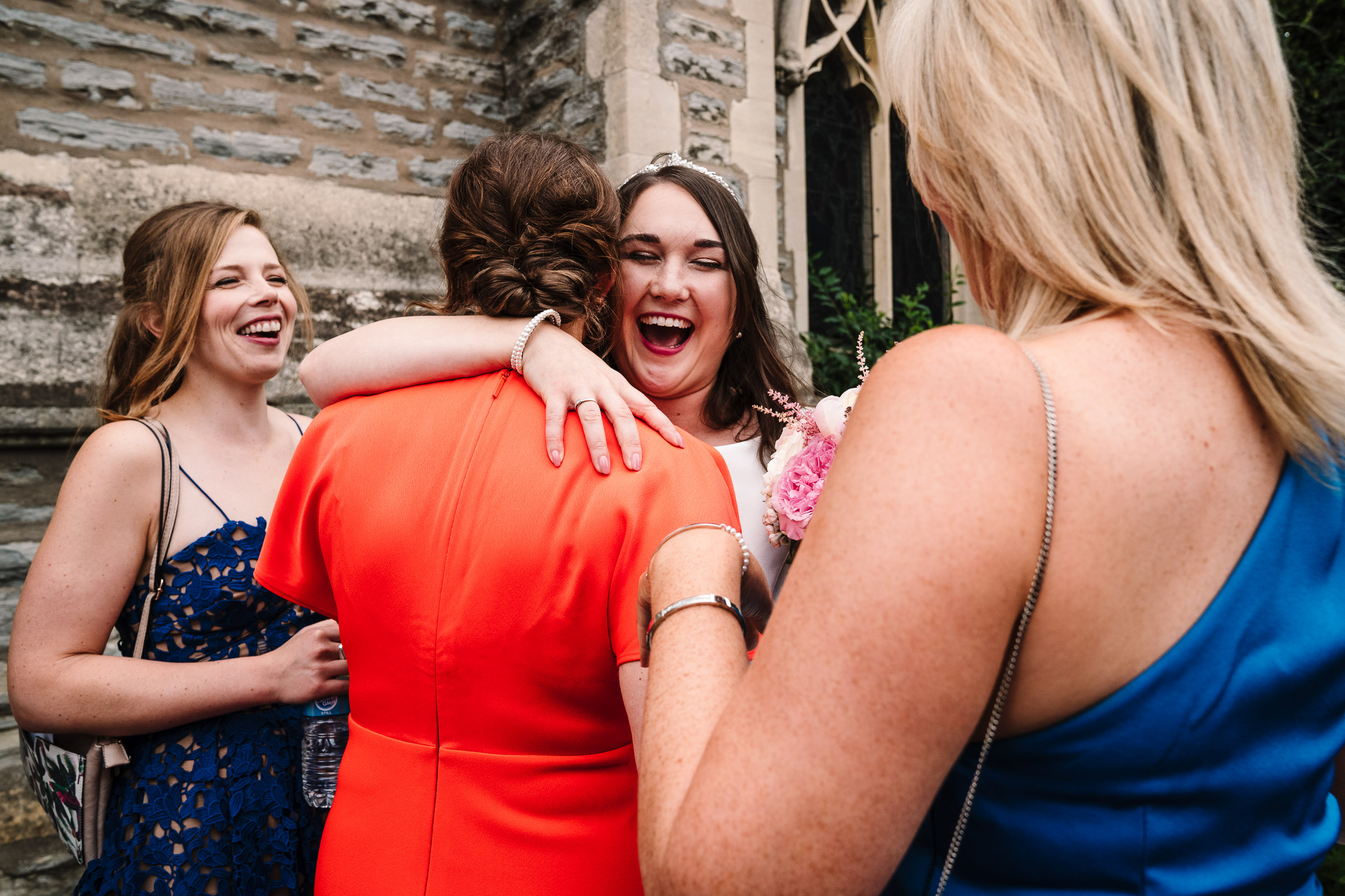 bride hugging guest outside church