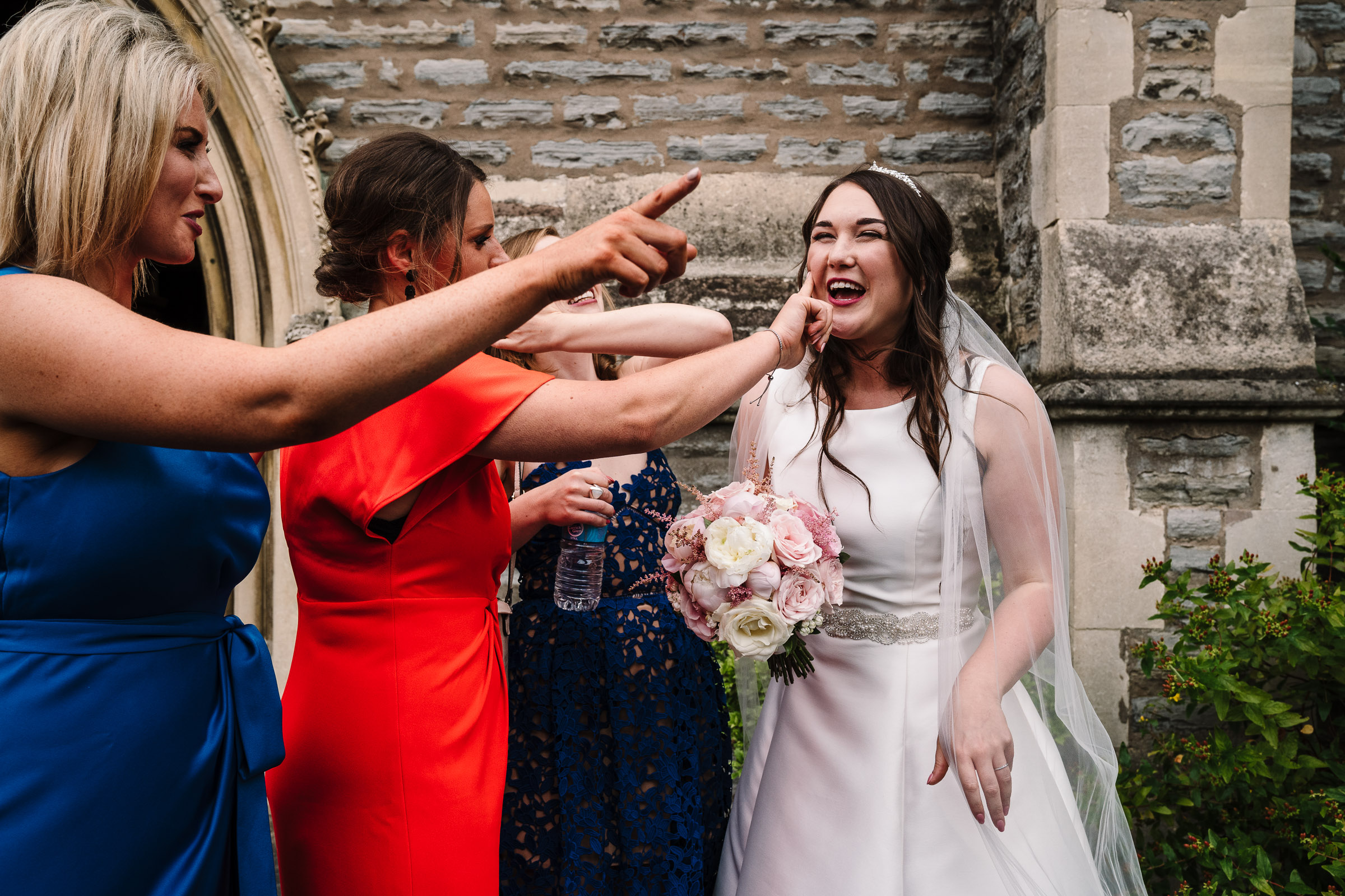 guests wiping lipstick off brides face after kissing her