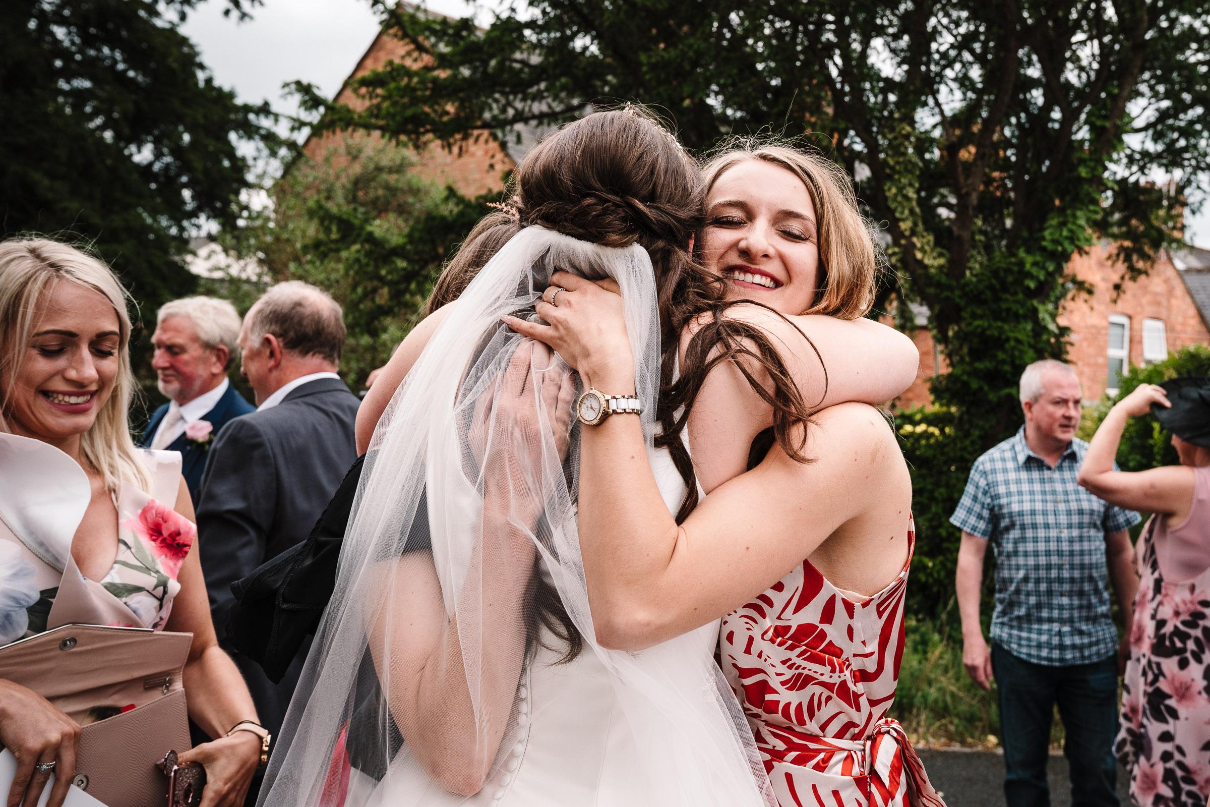 guests hugging bride after wedding ceremony
