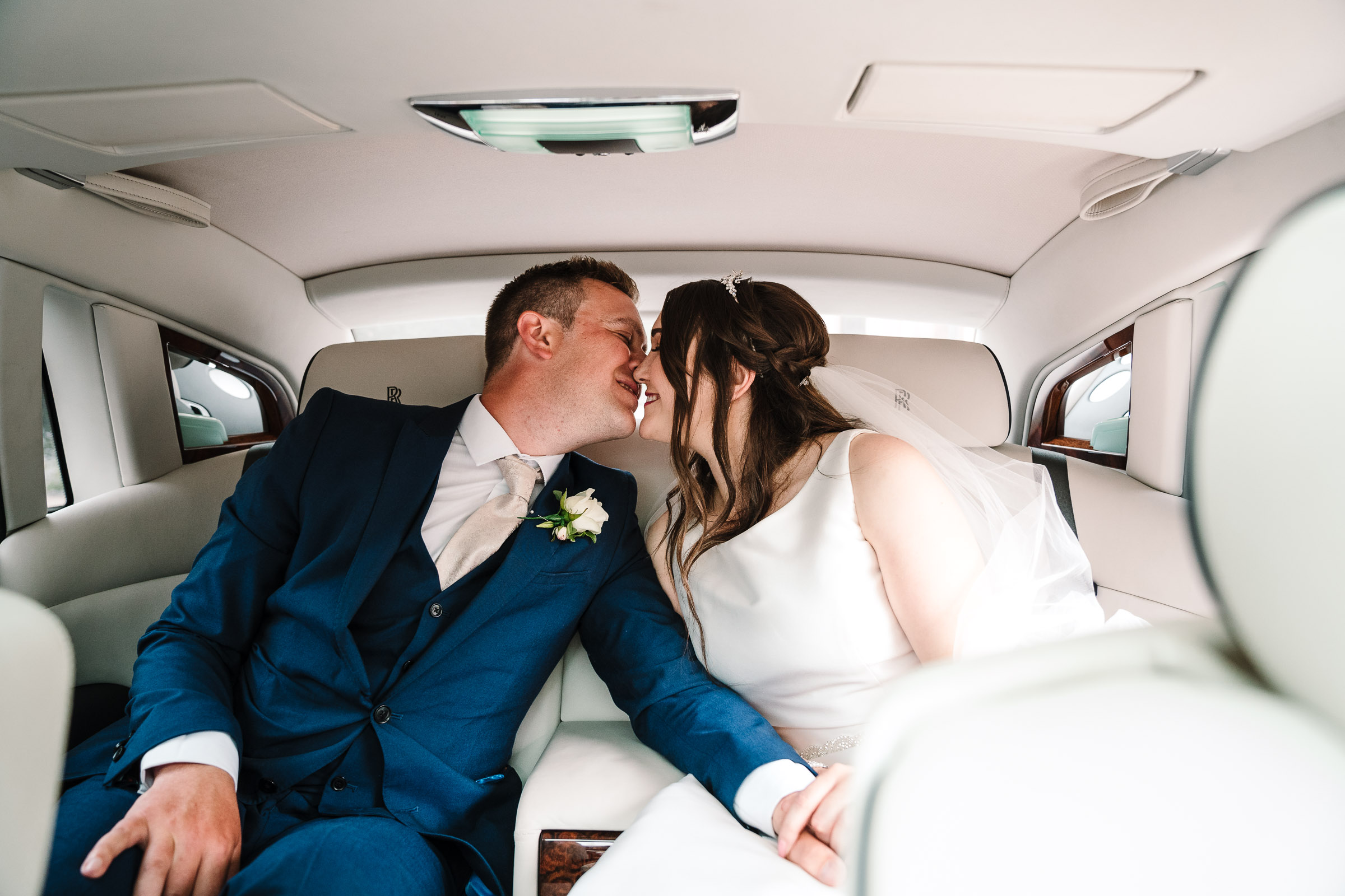 bride and groom kissing in wedding car at the wood norton
