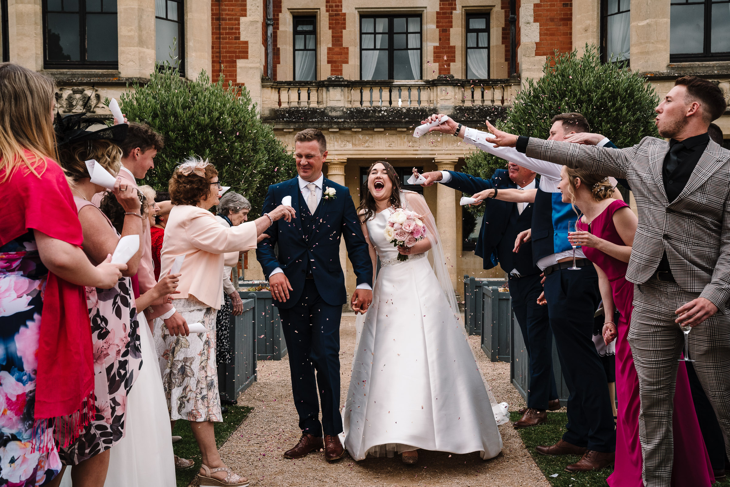 bride and groom laughing as they walk through confetti at the wood norton
