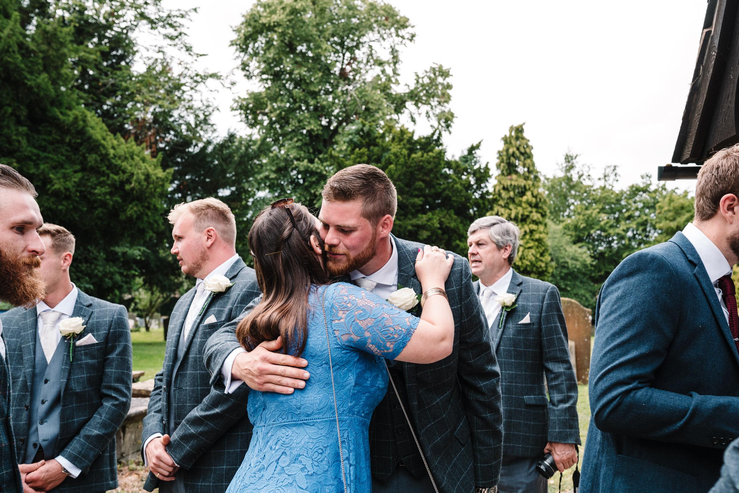 groom greeting guests before church wedding