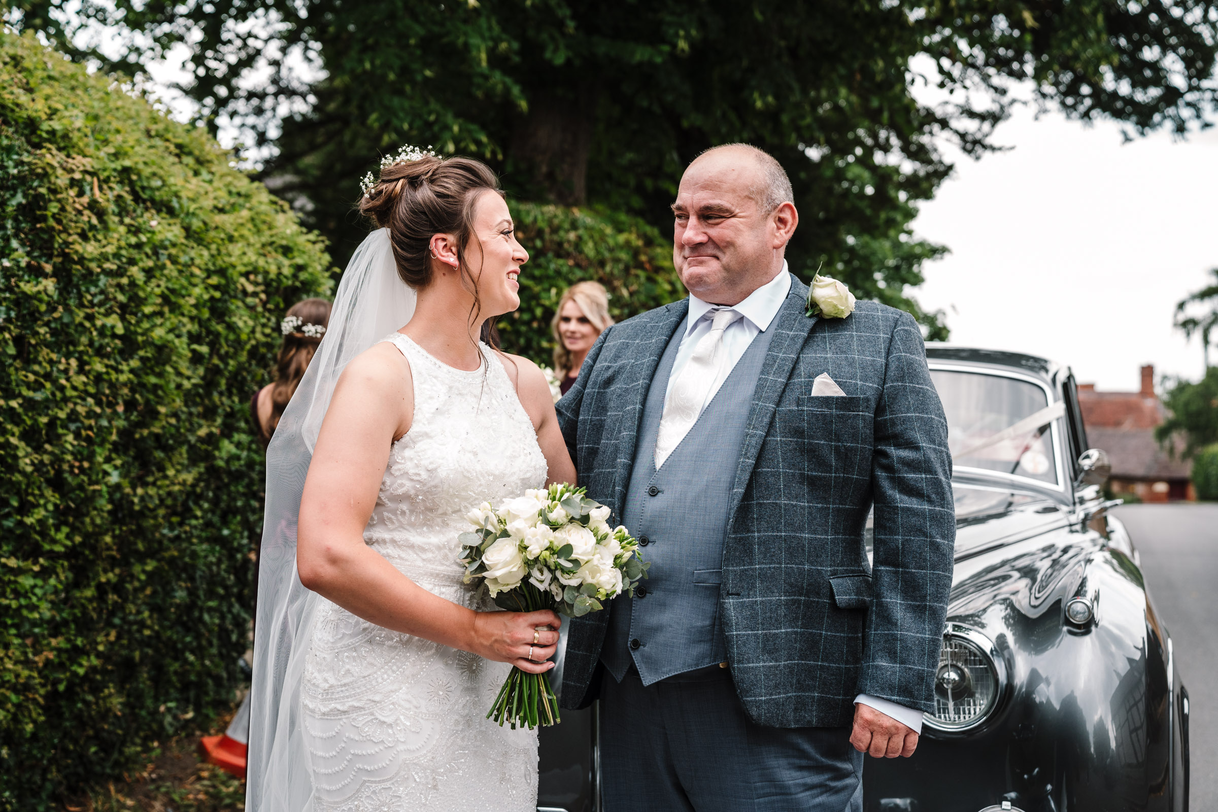 proud dad smiling at his daughter as they get ready to enter church wedding