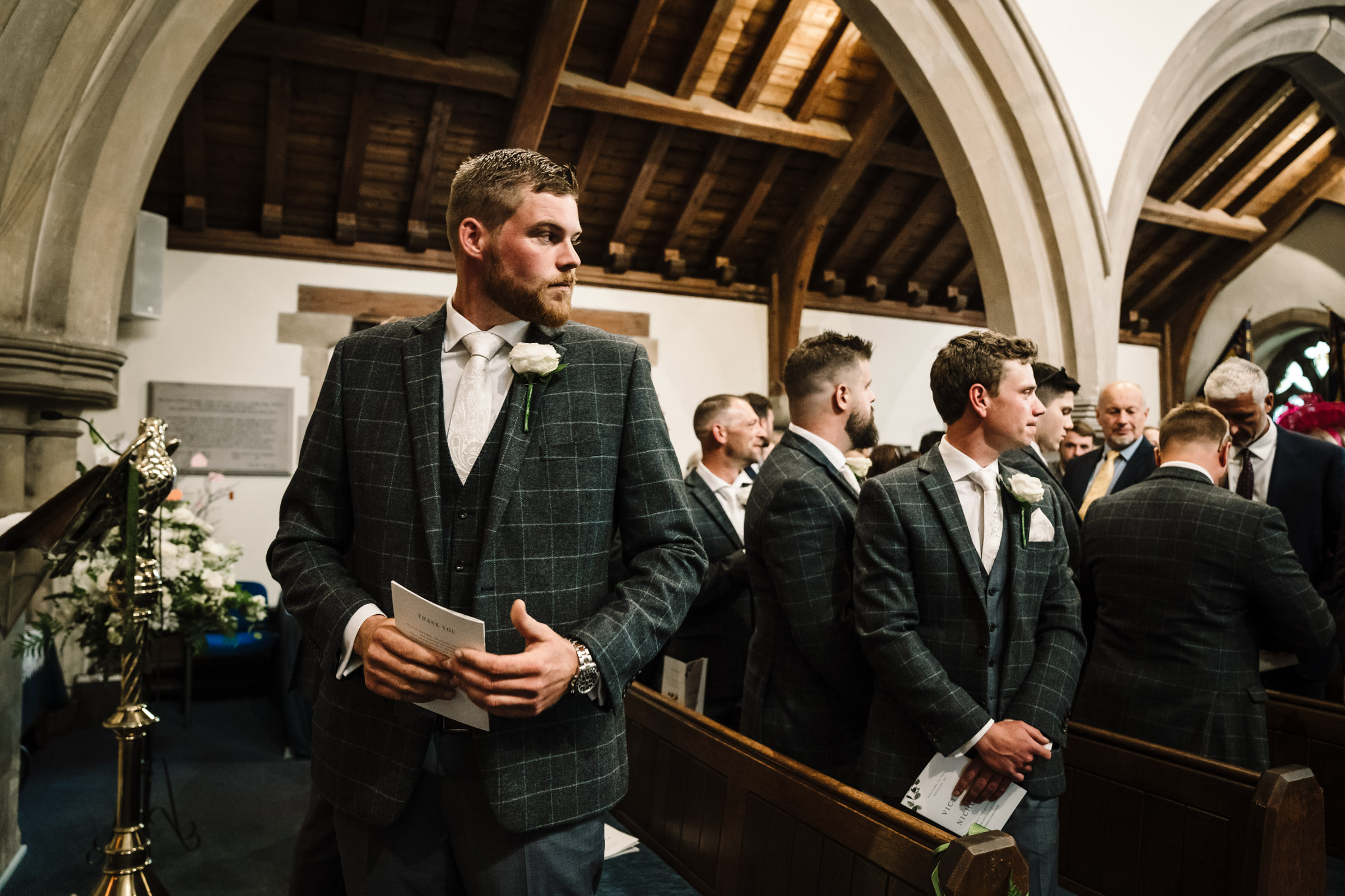 groom looking back at the aisle to watch bride entering church