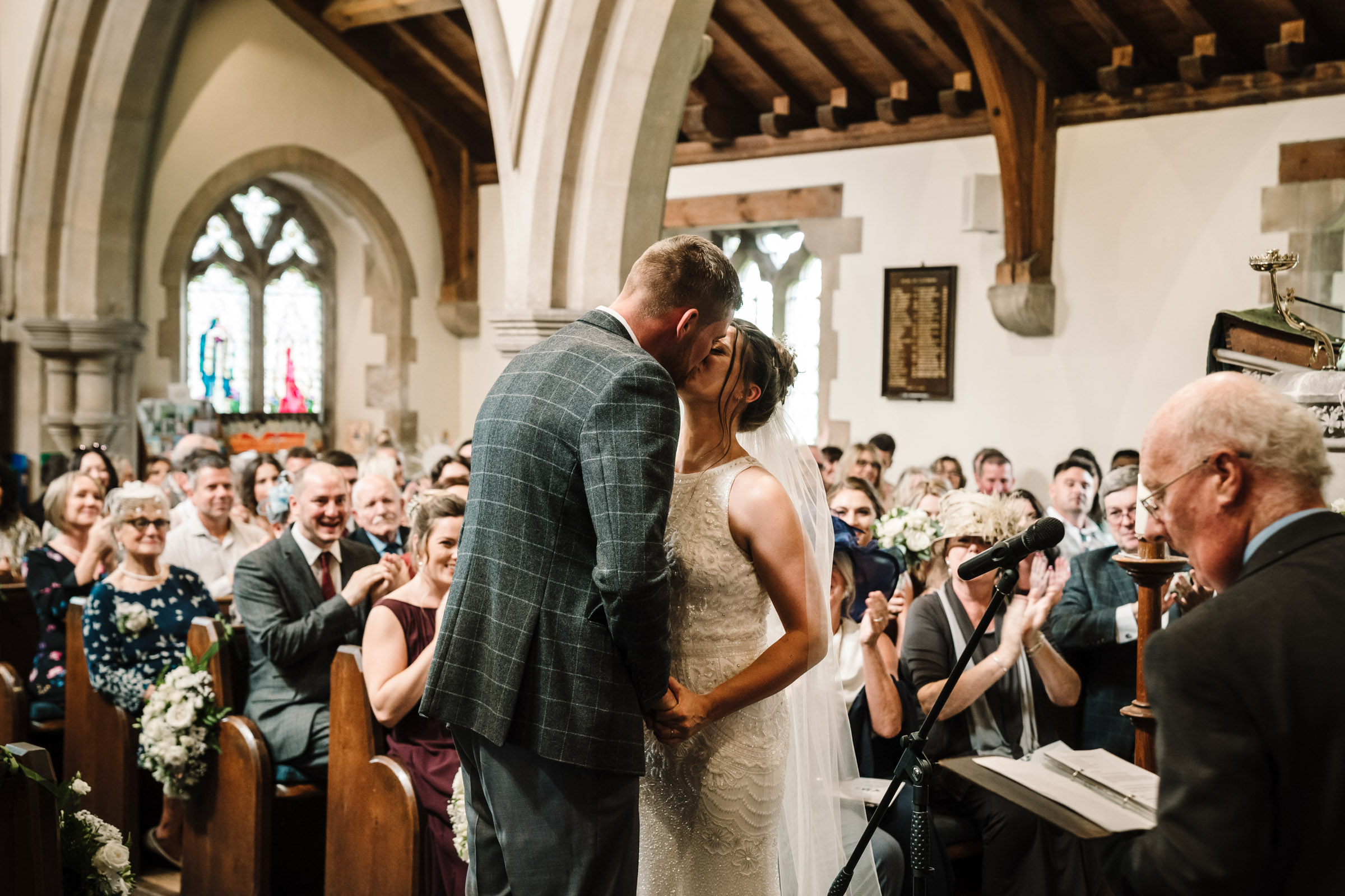 bride and groom first kiss as husband and wife, church wedding ceremony