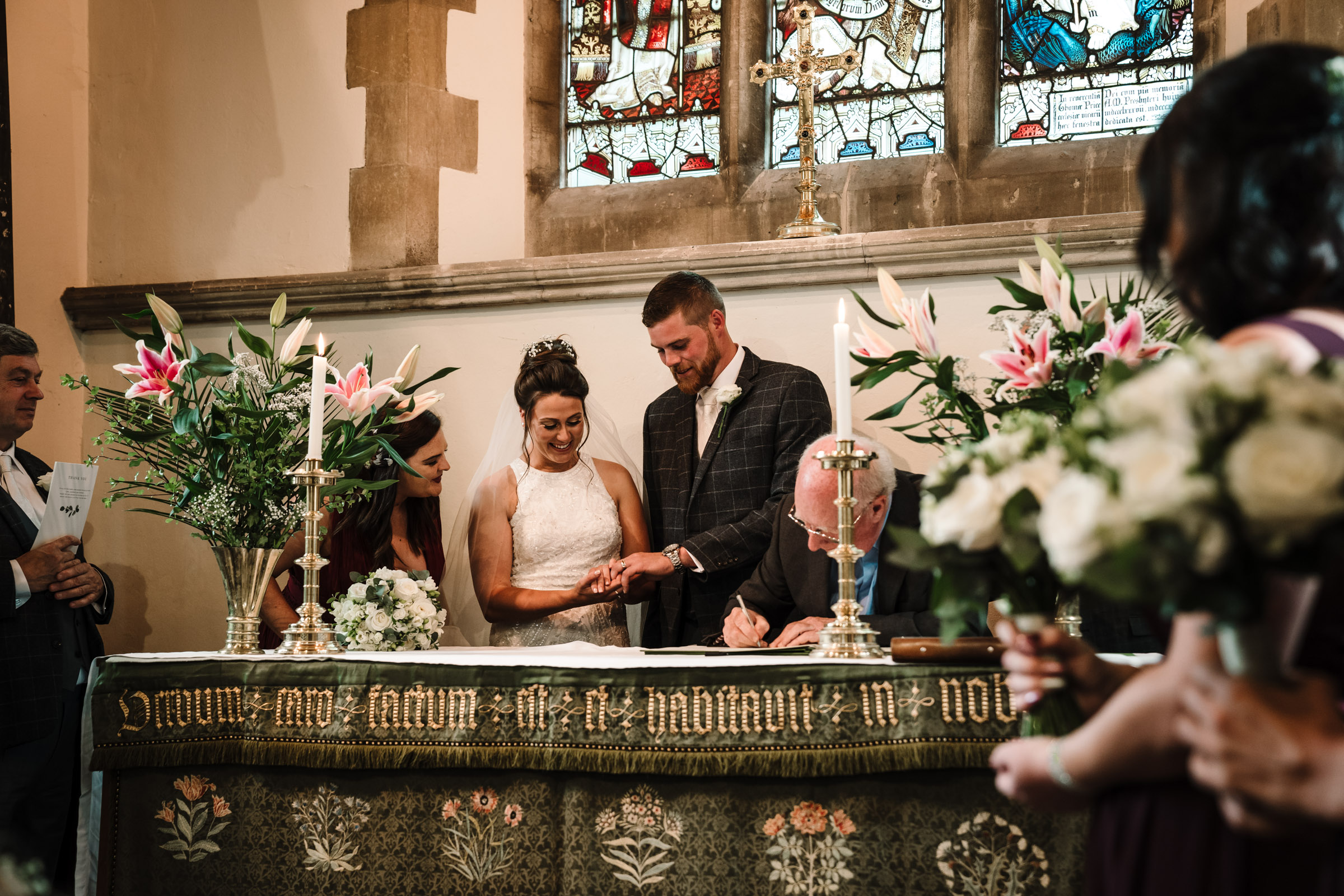 bride and groom at the alter, looking at their wedding rings as they sign the register