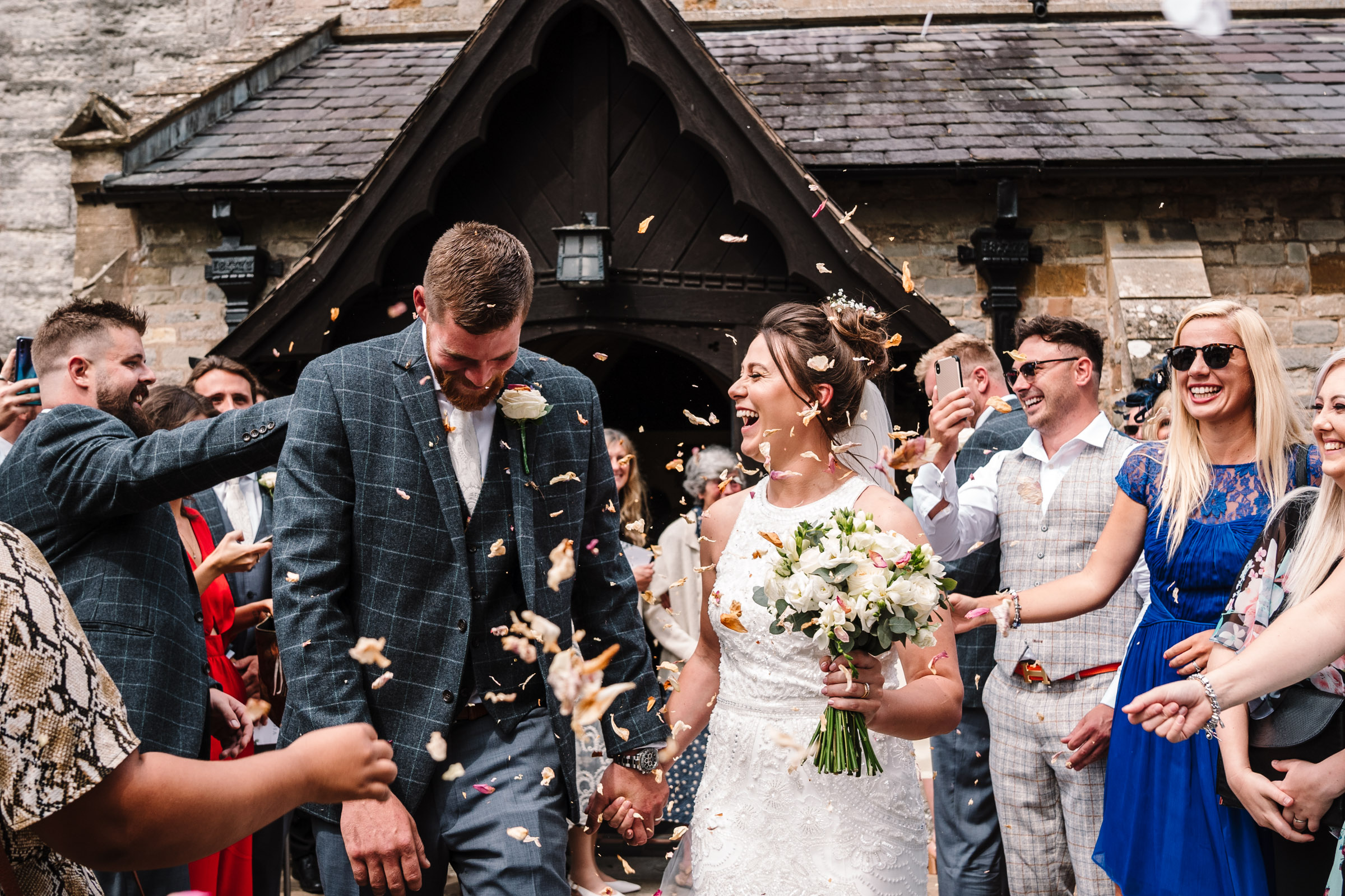 bride and groom laughing as confetti is thrown
