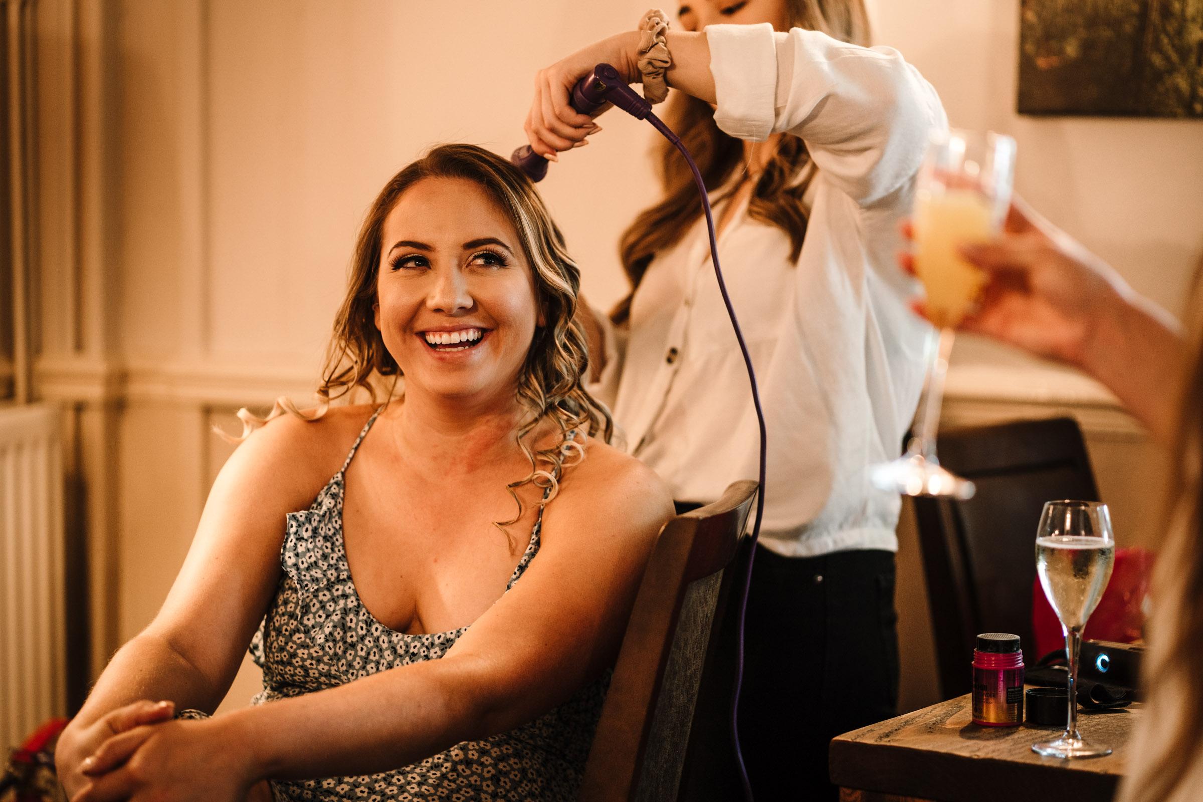 bridesmaid having her hair done during bridal prep
