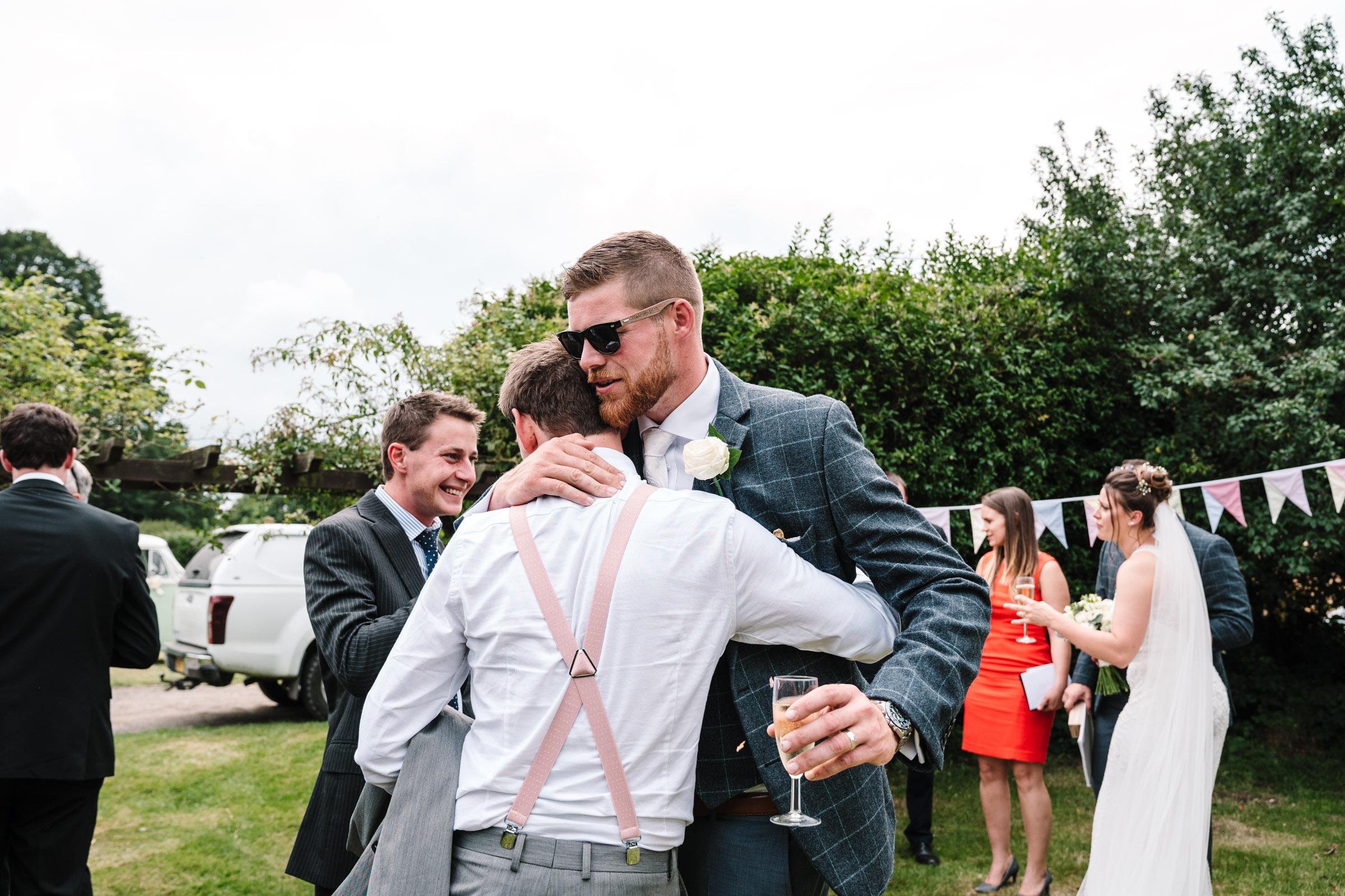 groom hugging friend during wedding reception