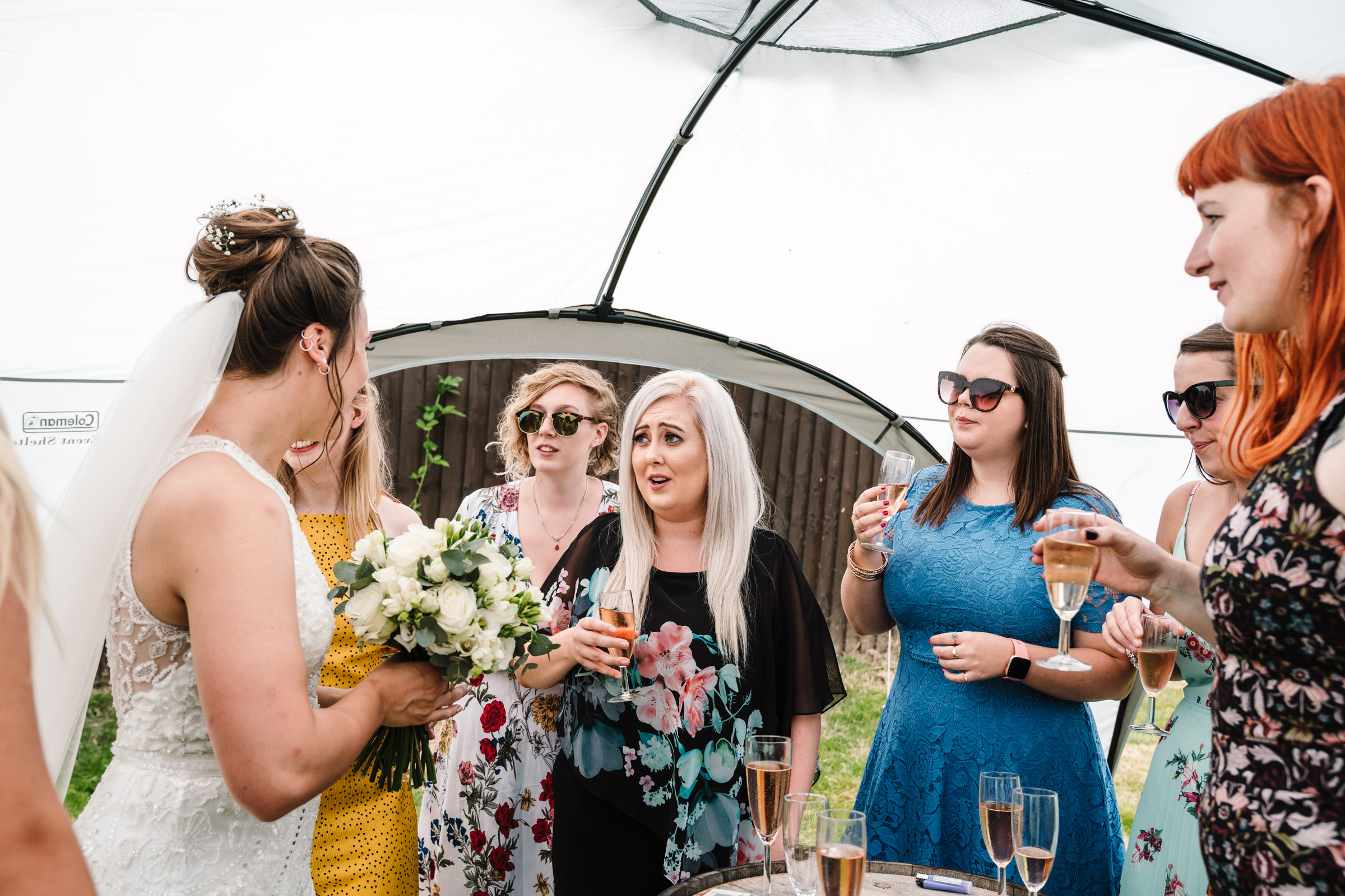 guests chatting to bride at tipi wedding reception