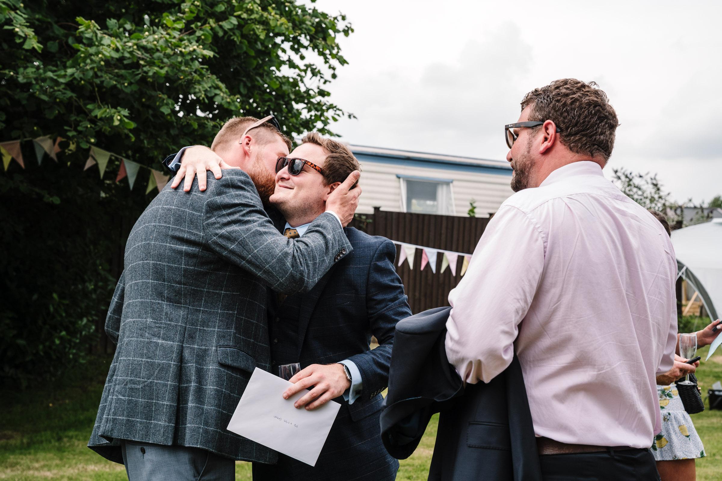 groom kissing friend at tipi wedding