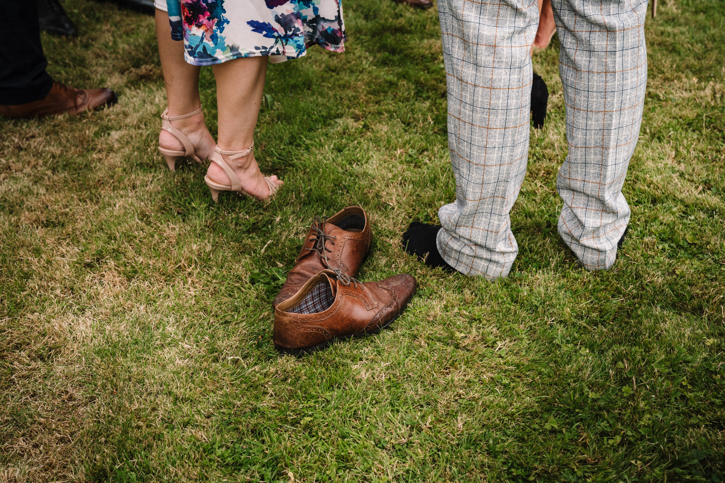 shoes on grass, taken off at wedding reception