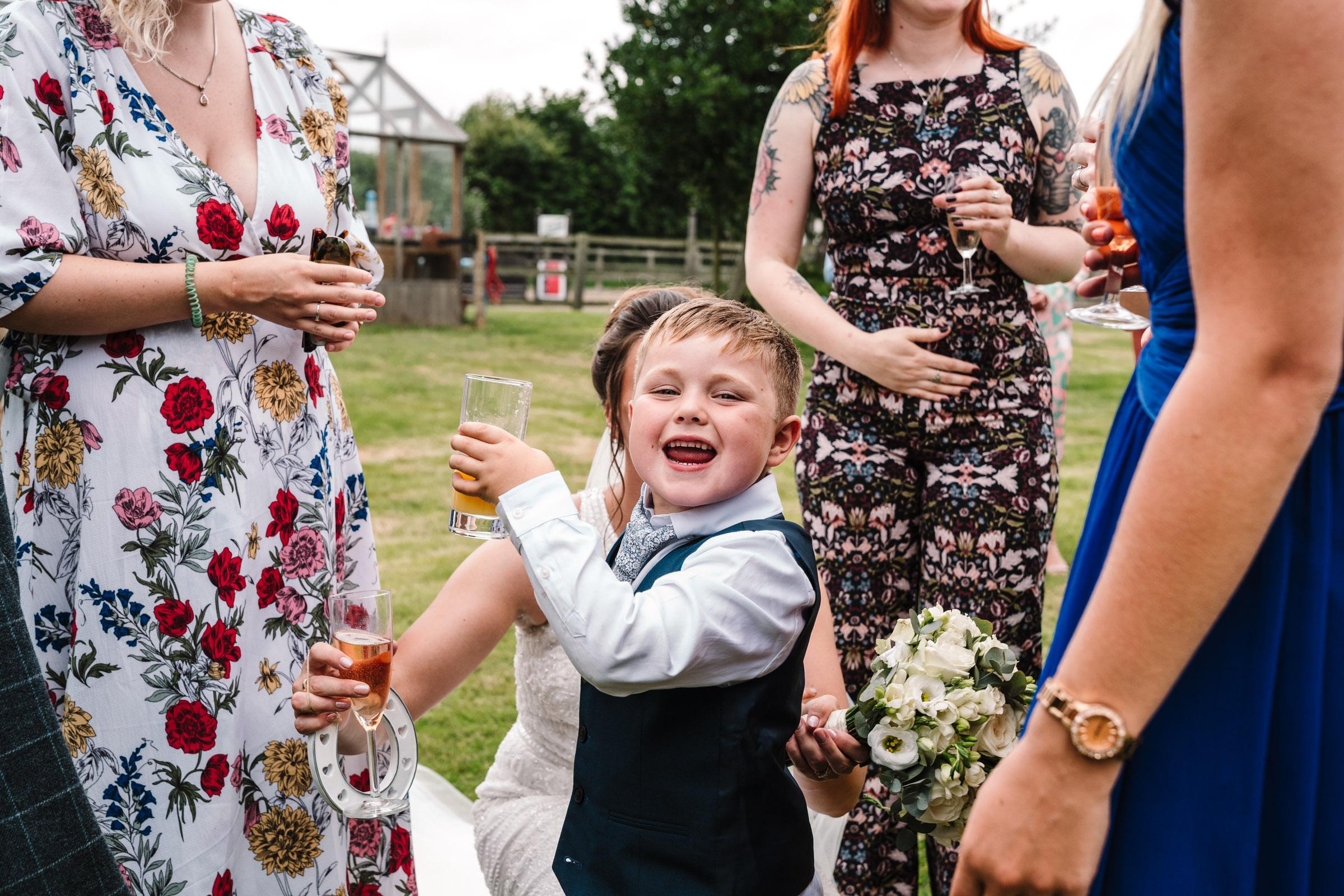 page boy saying cheers at wedding