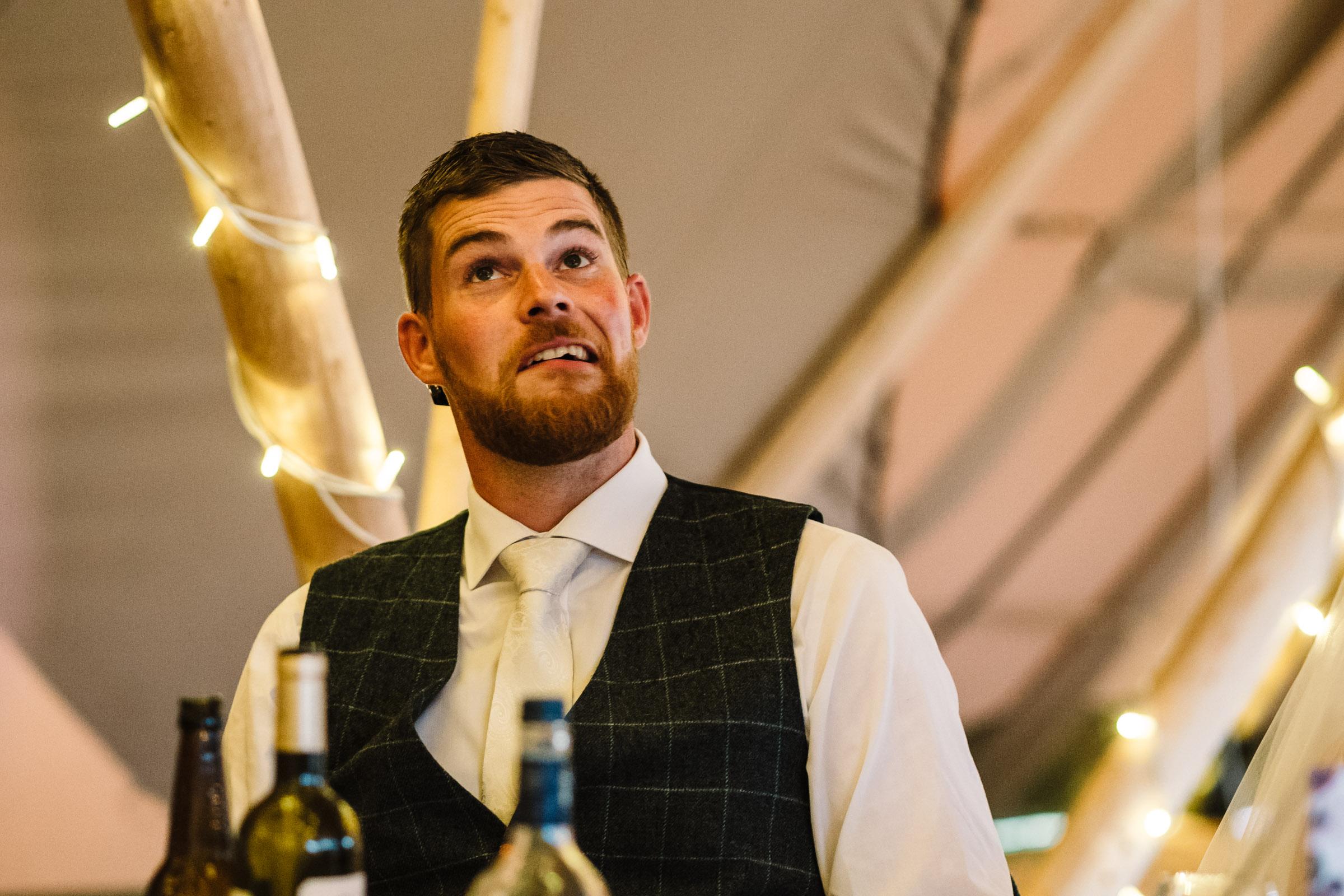 groom pulling funny face during wedding speech