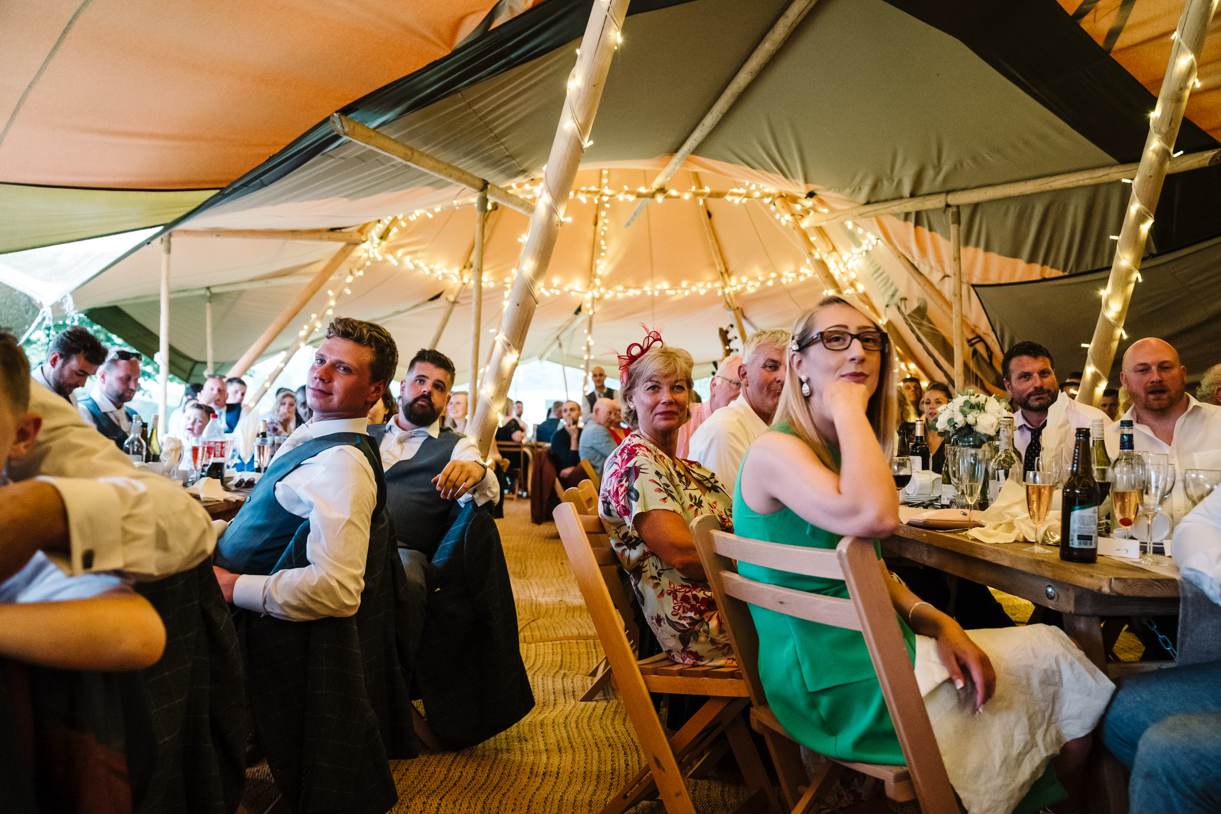 guest at tipi wedding listening to speeches